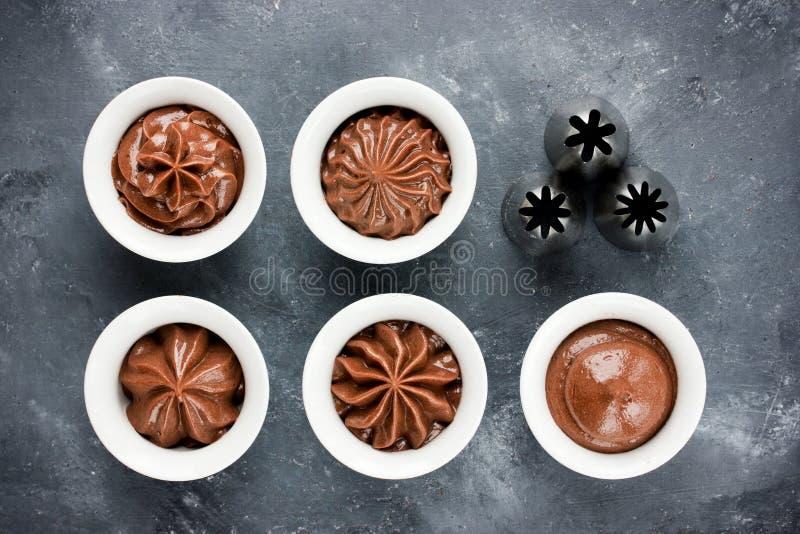 Chocolate que hiela remolinos y la diversa boca de la confitería del metal fotografía de archivo libre de regalías