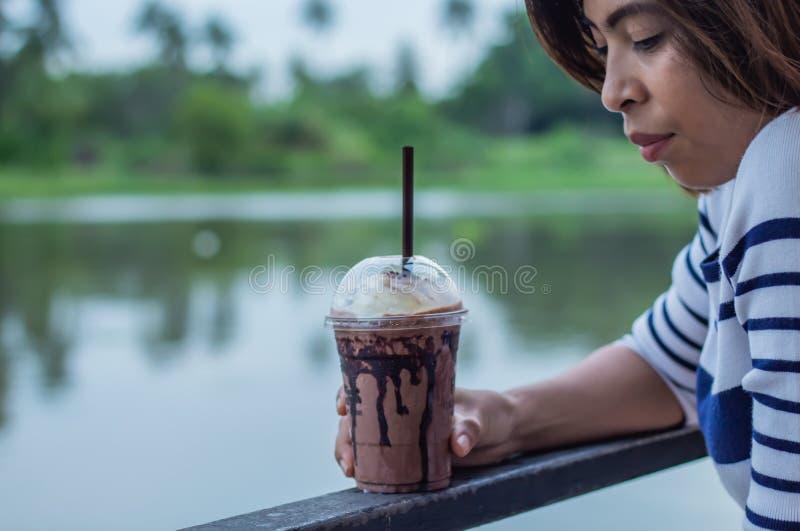 Chocolate que refresca a mano mujeres y la opinión del río imagenes de archivo