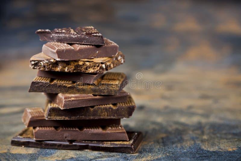 Chocolate quebrado empilhado no fundo preto As partes da barra de chocolate empilham o pó da canela do witn imagem de stock