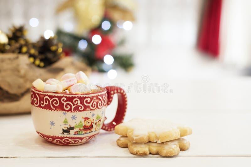 Chocolate quente com doces do marshmallow As cookies do Natal deram forma nos flocos de neve, em cones dourados e em luzes da árv fotos de stock royalty free
