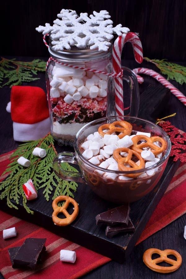 Chocolate quente com marshmallows e pretzeis em um copo e uma mistura seca para preparar a bebida imagens de stock