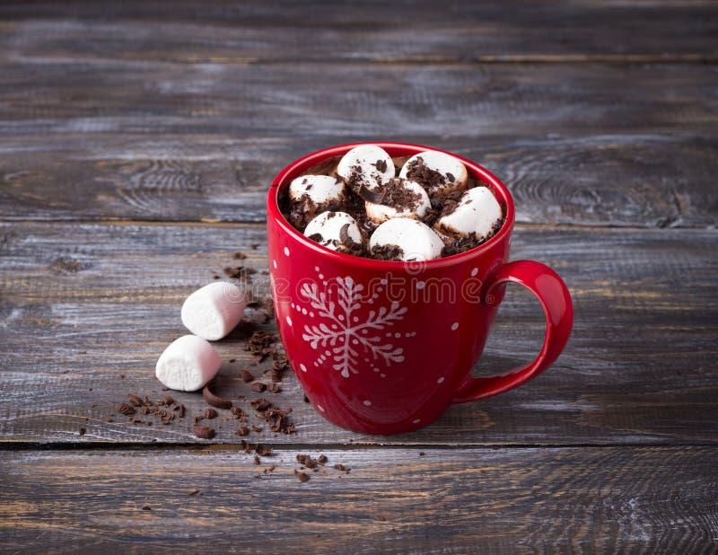 Chocolate quente com marshmallows e chocolate raspado em uma caneca vermelha em uma tabela de madeira fotografia de stock
