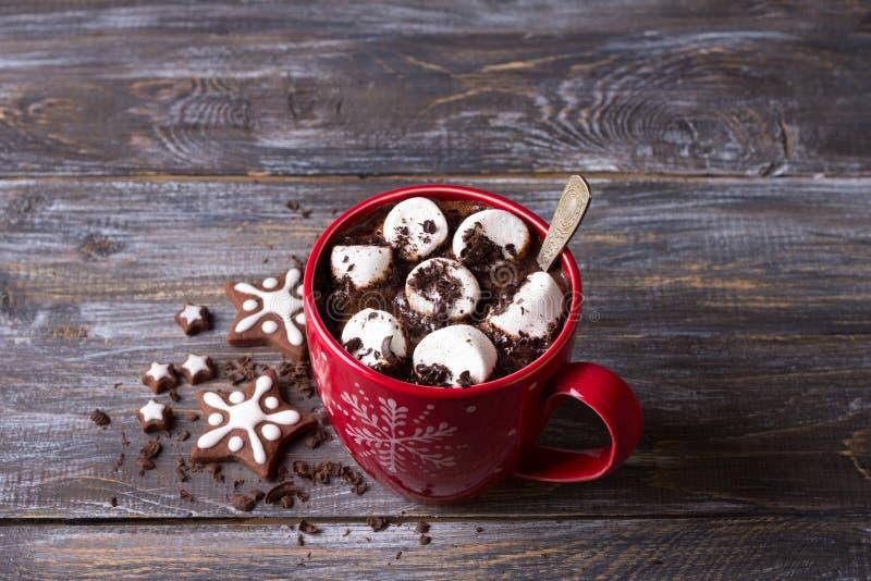 Chocolate quente com marshmallows e chocolate raspado em uma caneca vermelha em uma tabela de madeira imagem de stock royalty free