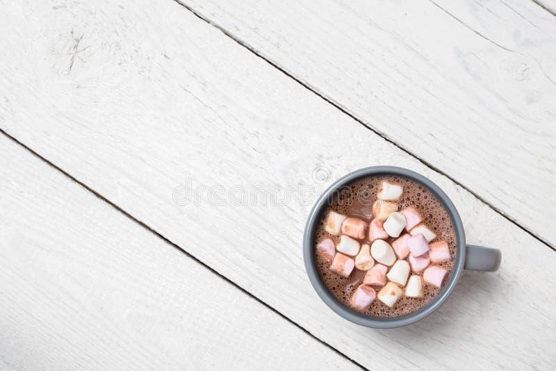 Chocolate quente com marshmallows pequenos em uma caneca cerâmica azul-cinzenta na madeira pintada branca de cima de Espa?o para  imagem de stock royalty free