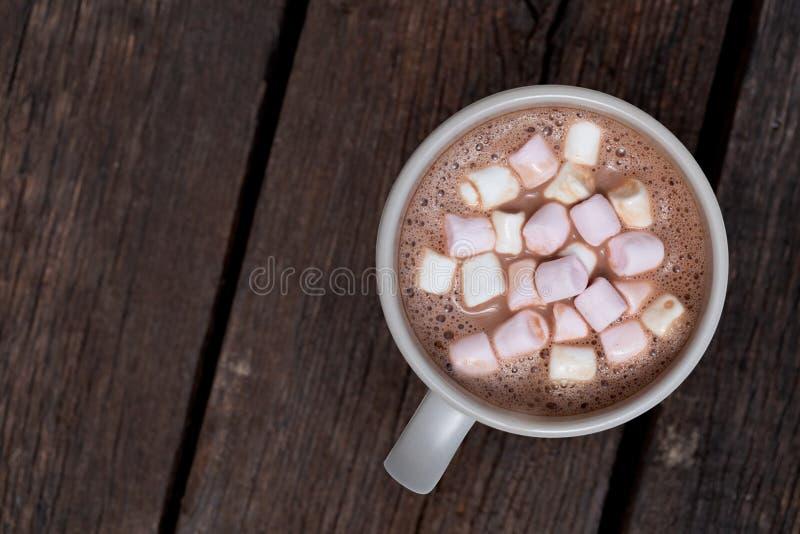 Chocolate quente com marshmallows pequenos em uma caneca cerâmica cinzenta isolada na madeira marrom escura de cima de Espa?o par imagens de stock
