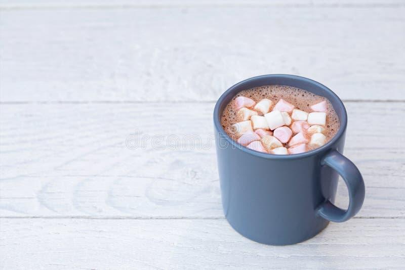 Chocolate quente com os marshmallows pequenos do rosa e os brancos em uma caneca cerâmica azul-cinzenta na madeira pintada branca fotografia de stock
