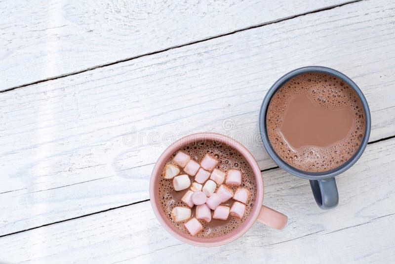 Chocolate quente em duas canecas, um com os marshmallows pequenos, isolados na madeira pintada branca de cima de Espa?o para o te imagens de stock