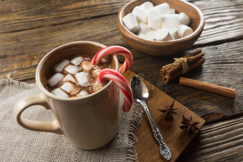 Chocolate quente, marshmallow e canela na tabela rústica imagem de stock royalty free