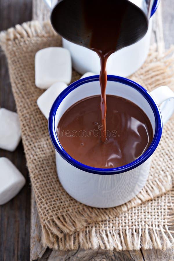 Chocolate quente que derrama em um copo imagens de stock