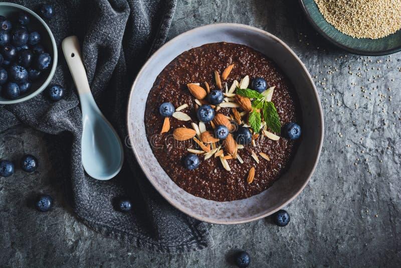 Chocolate Quinoa porridge with almonds and blueberry. Healthy chocolate Quinoa porridge with coconut milk, honey, almonds and blueberry stock image