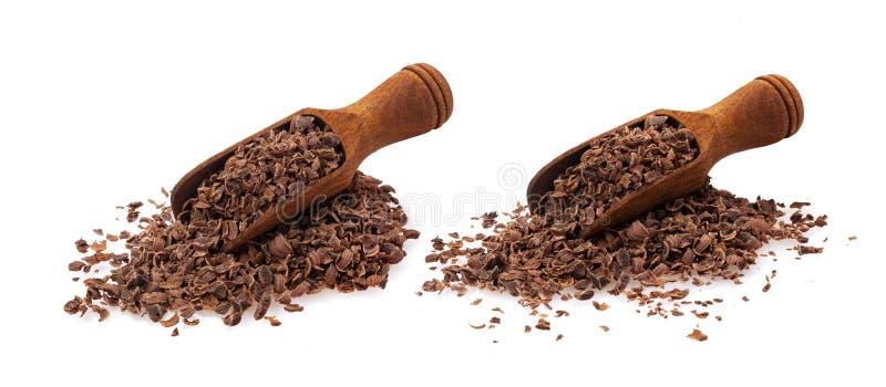 Chocolate raspado Pilha do chocolate à terra na colher de madeira isolada no fundo branco, close up imagens de stock royalty free