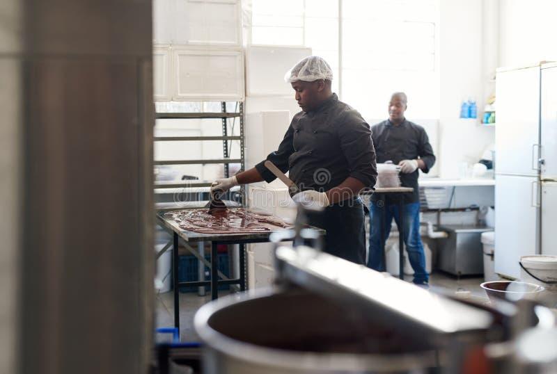 Chocolate refrigerando do trabalhador em uns confeitos que fazem a fábrica imagens de stock