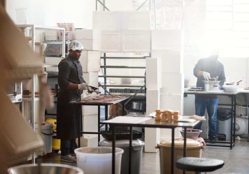 Chocolate refrigerando do trabalhador em uns confeitos que fazem a tabela da fábrica foto de stock royalty free