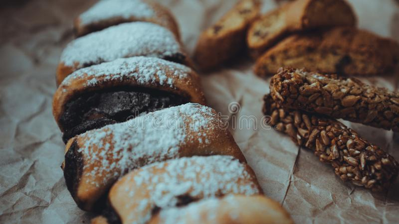 Chocolate Rolls sprinkled with powdered sugar. Background of craft paper. Chocolate Rolls with a delicious filling and delicious crackers, sprinkled with stock photography