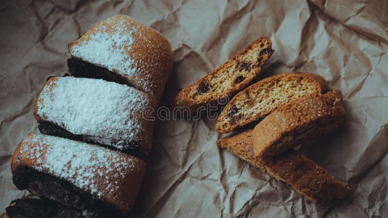 Chocolate Rolls sprinkled with powdered sugar. Background of craft paper. Chocolate Rolls with a delicious filling and delicious crackers, sprinkled with royalty free stock images