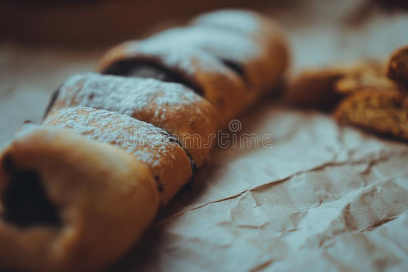 Chocolate Rolls sprinkled with powdered sugar. Background of craft paper. Freshly Baked Chocolate Rolls with a delicious filling, sprinkled with powdered sugar stock images