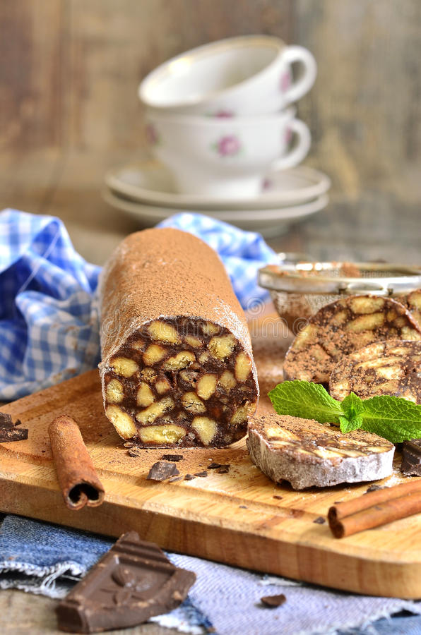 Chocolate salami with biscuits. Chocolate salami with biscuits on a cutting board royalty free stock photo