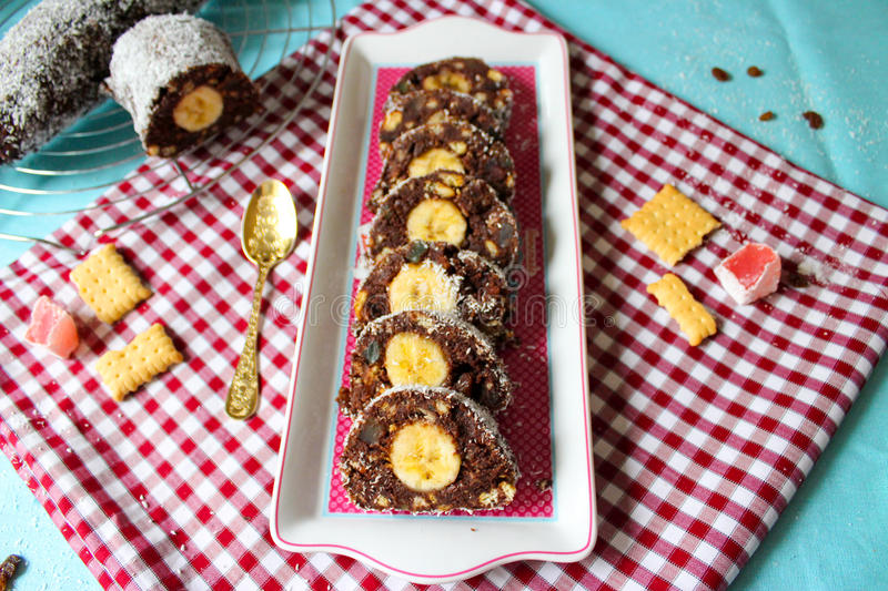 Chocolate salami roll with banana and coconut slices stock photo
