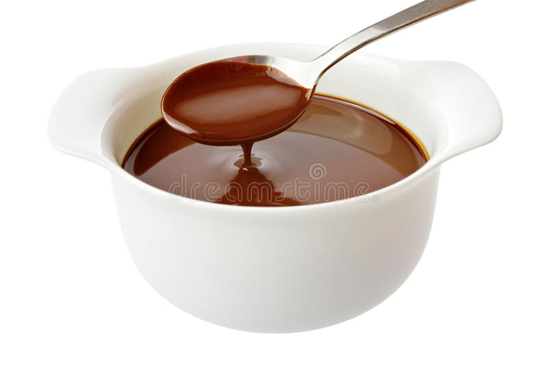 Chocolate Sauce. Trickling from a spoon into a bowl, isolated on white royalty free stock photography