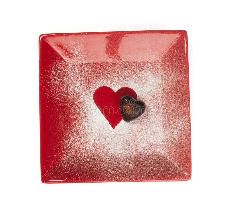 Chocolate in the shape of hearts. Set in red plate royalty free stock photo