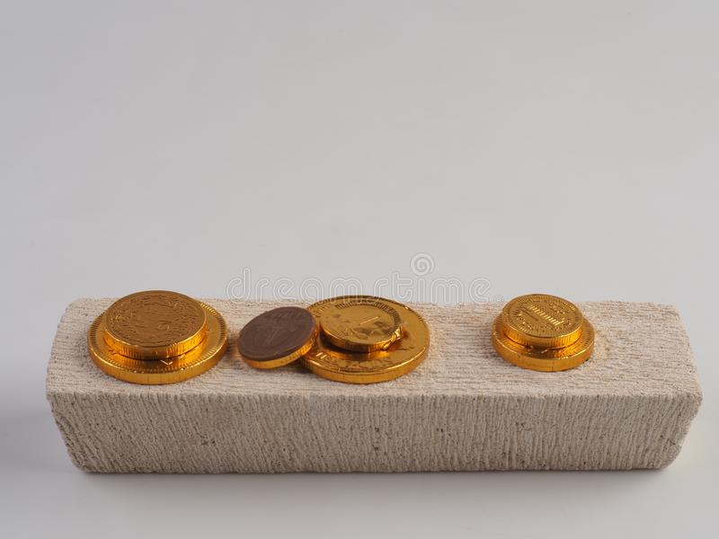 Chocolate shaped like coins in gold foil sheet isolated on white background. Chocolate shaped like coins in gold foil sheet on block rock, isolated on the white royalty free stock photography