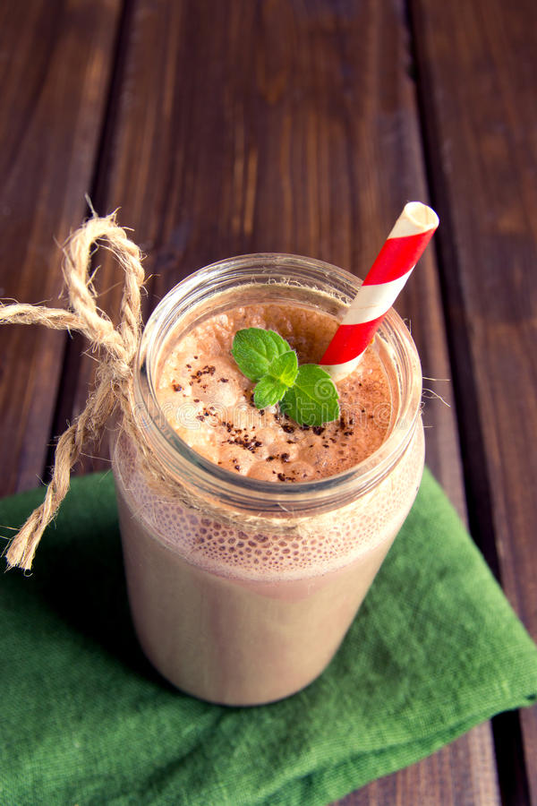 Chocolate smoothie (milkshake). With mint and straw in jar on dark wooden table royalty free stock photo