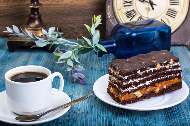 Chocolate sponge cake with caramel and nuts on blue background royalty free stock photo