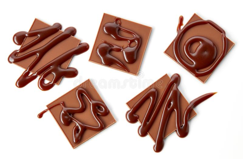 Chocolate squares decorated with chocolate sauce stock image