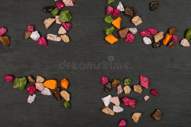 Chocolate stone candy on grey stone. Lot of whole sweet chocolate stone flatlay on grey stone stock photos