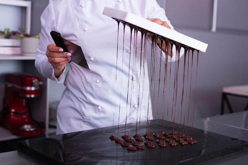 Professional chocolatier making nice little chocolate sweets. Chocolate sweets. Professional chocolatier feeling very busy while making nice little chocolate royalty free stock photography