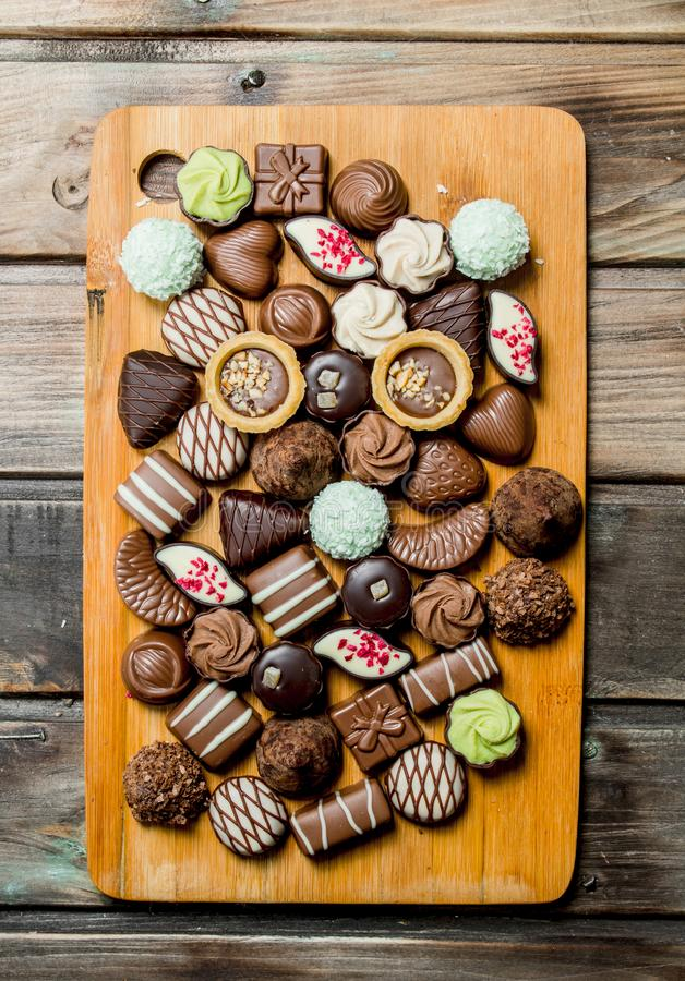 Chocolate sweets on a wooden Board royalty free stock images