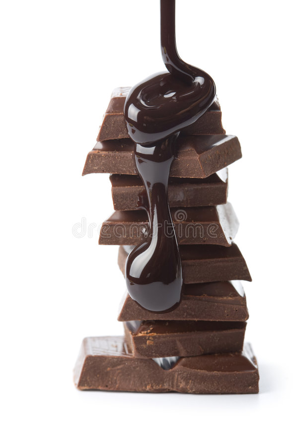 Chocolate syrup being poured onto chocolate pieces