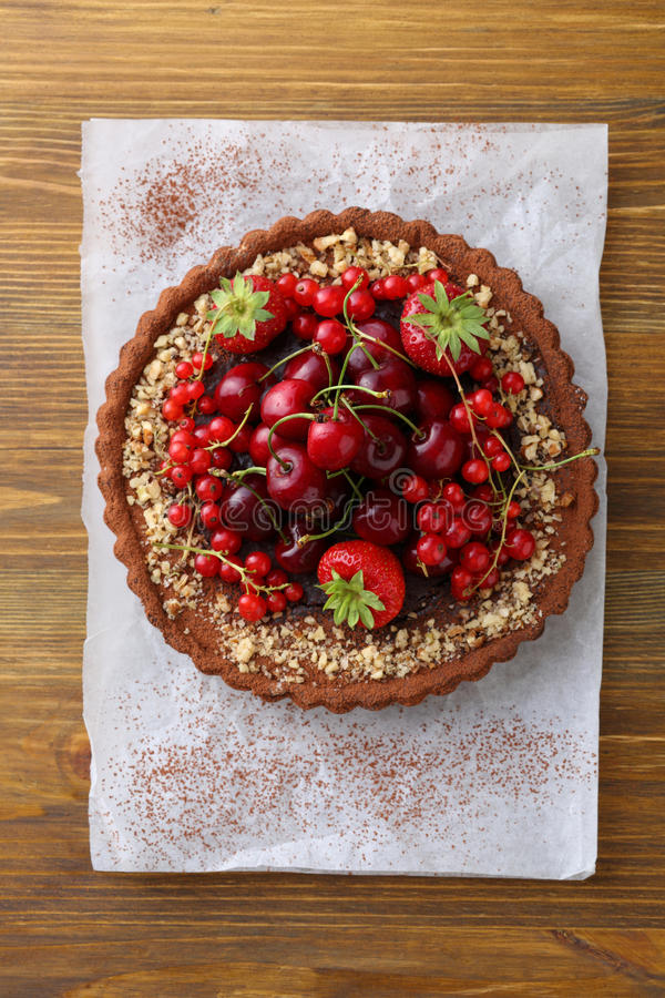 Chocolate tart decorated with fresh berries. Top view royalty free stock images