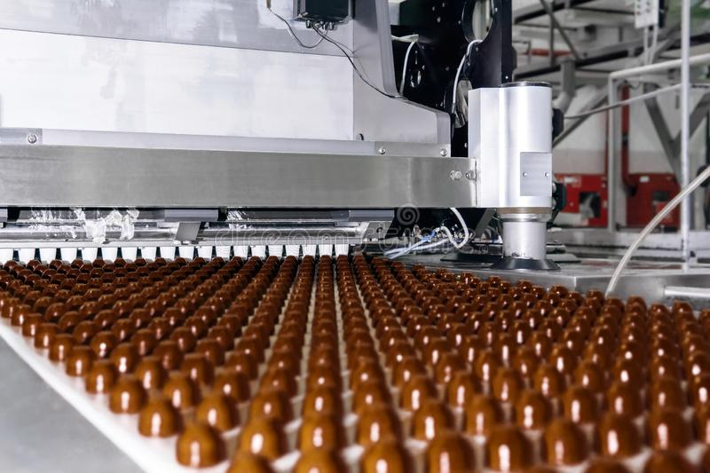 Chocolate toppings on the conveyor of a confectionery factory close-up. Rows of toppings for chocolates manufactured by machine, on a conveyor of a chocolate royalty free stock images