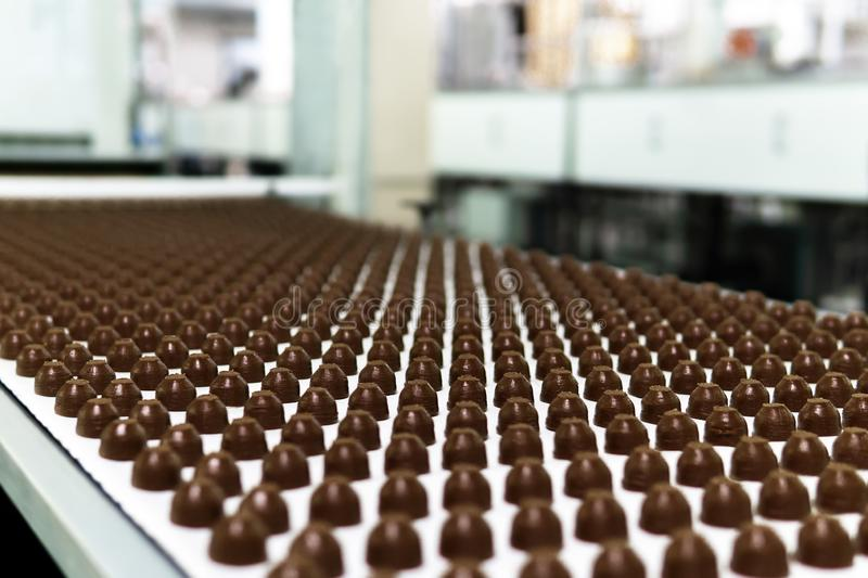 Chocolate toppings on the conveyor of a confectionery factory close-up. Rows of toppings for chocolates manufactured by machine, on a conveyor of a chocolate stock photo