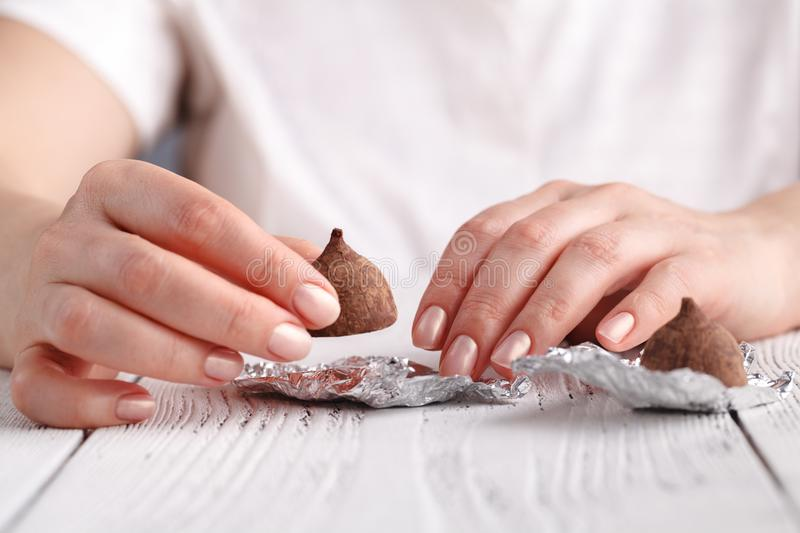 Chocolate truffle in female hands, close up view royalty free stock photos