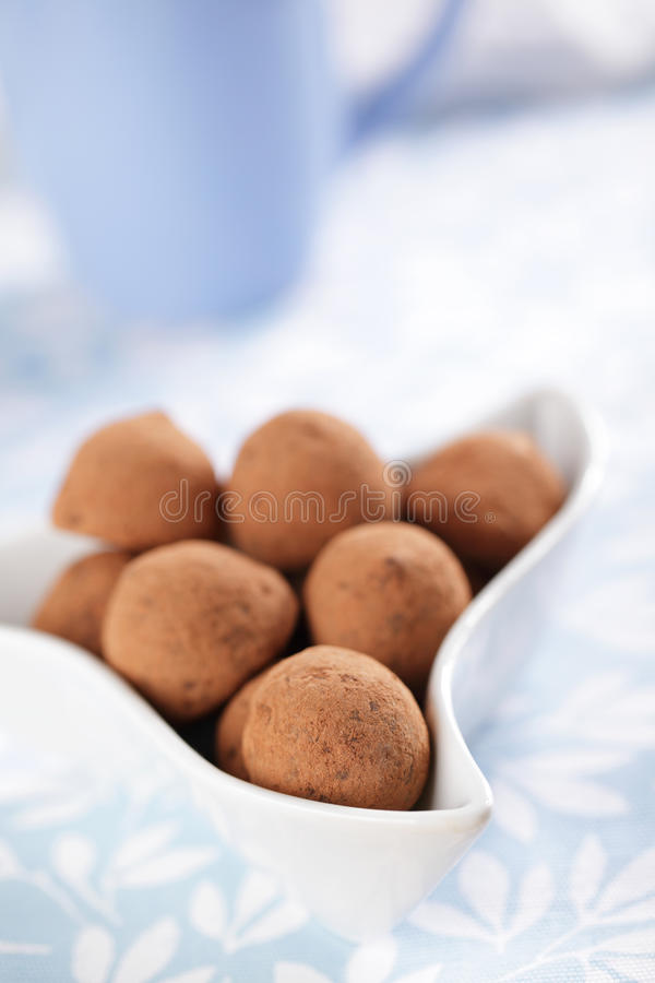 Chocolate truffles. In the white bowl closeup stock photography