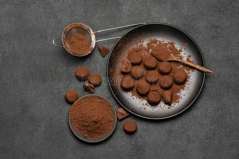 Chocolate truffles candies and cocoa powder on dark concrete background stock images
