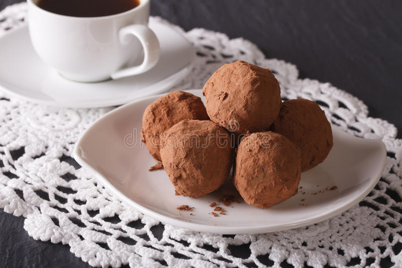 Chocolate truffles on a plate and coffee close-up on the table. stock image