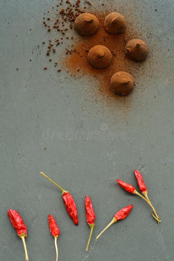 Cocoa truffles and red hot chili peppers royalty free stock photos