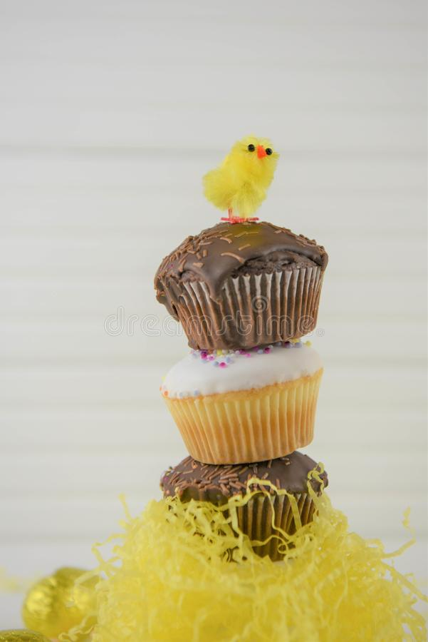 Vertical stack of Easter cakes on white. Chocolate and vanilla homemade cupcakes or fairy cakes with sprinkles. Stacked in a vertical heap with Easter chick and royalty free stock photo