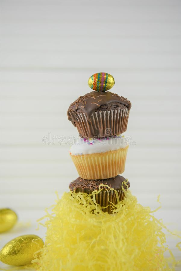 Vertical stack of mini Easter cakes on white. Chocolate and vanilla homemade cupcakes or fairy cakes with sprinkles. Stacked in a vertical heap with Easter stock image