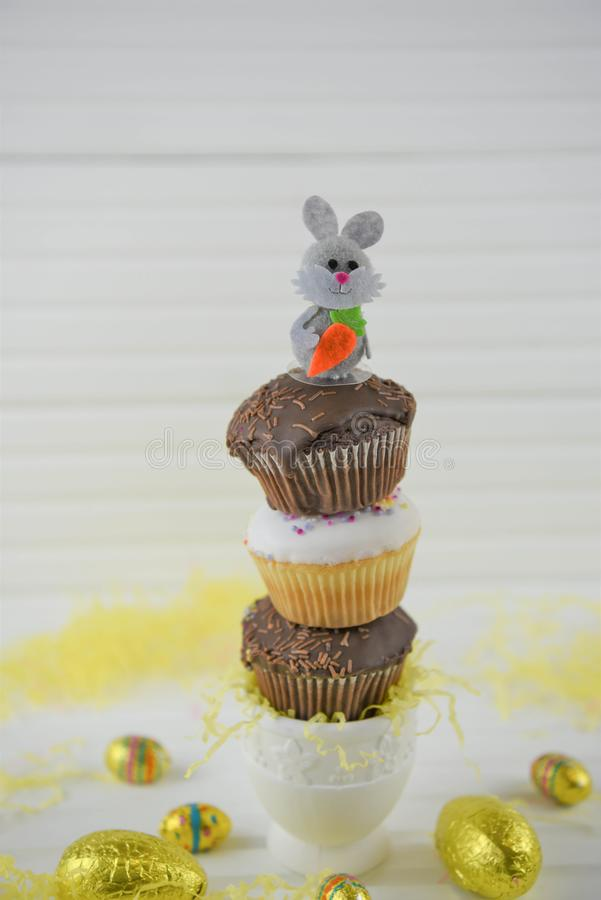 Vertical stack of mini Easter cakes on white. Chocolate and vanilla homemade cupcakes or fairy cakes with sprinkles. Stacked in a vertical heap with eggcup base stock image