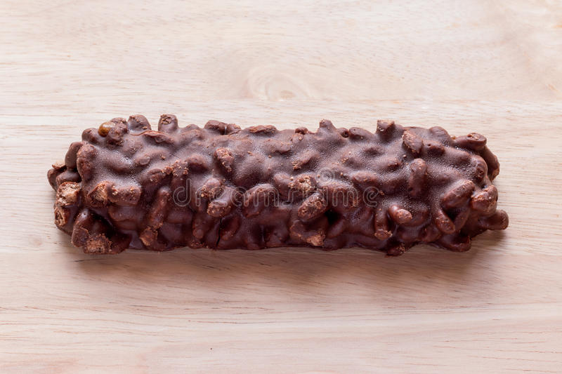 Chocolate wafer bars ingredients include almonds, cashews, cherries, raisins, cranberries, and honey. on wooden background. stock photos