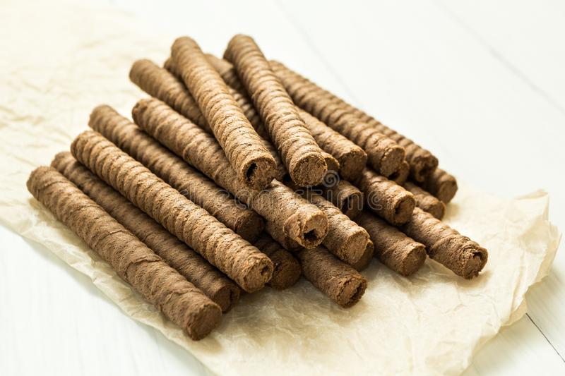 Chocolate wafer rolls on a wooden background royalty free stock photography