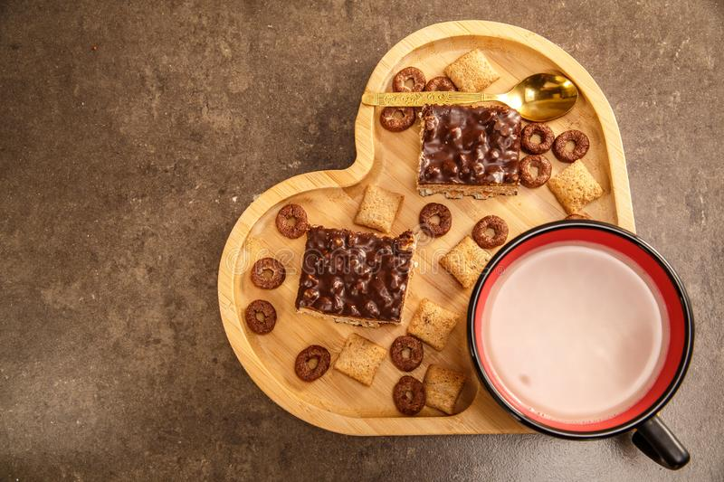 Chocolate wafers cookies in a wooden tray in the shape of a heart and a cup of hot chocolate. royalty free stock photography