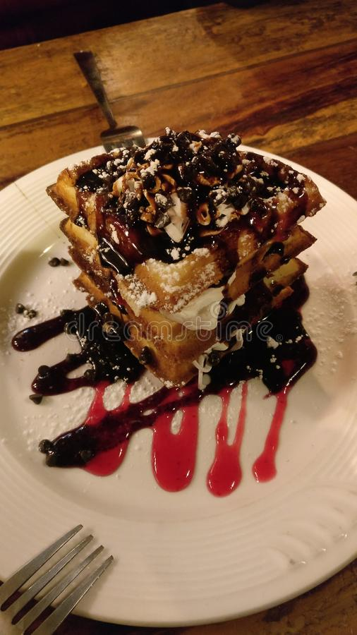 Chocolate Waffles. With sugar coating and Strawberry drizzle royalty free stock photography