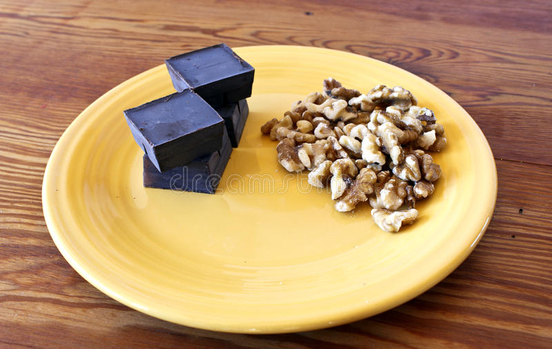 Chocolate and Walnut ingredients. On a yellow plate and wooden table royalty free stock images