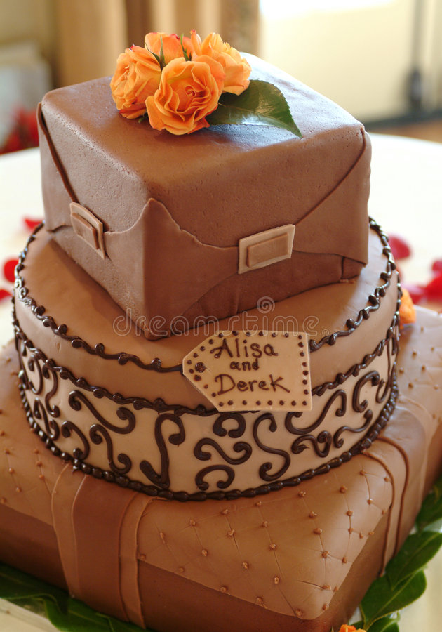 Chocolate wedding cake. Three-tiered chocolate wedding cake covered with rolled chocolate fondant, each layer a different shape and pattern using scrapbook stock photos