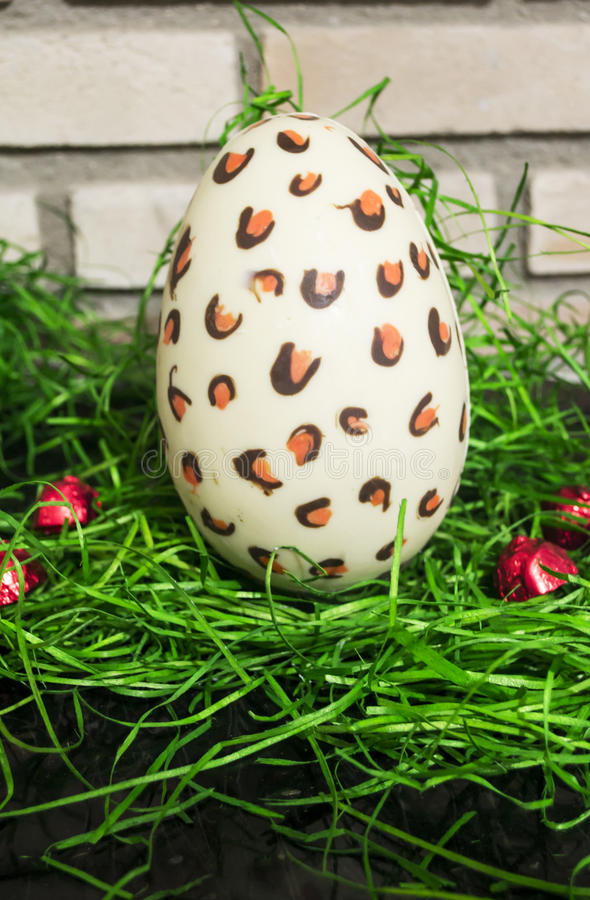 Chocolate white Easter egg with red bonbons and green 2 stock photography